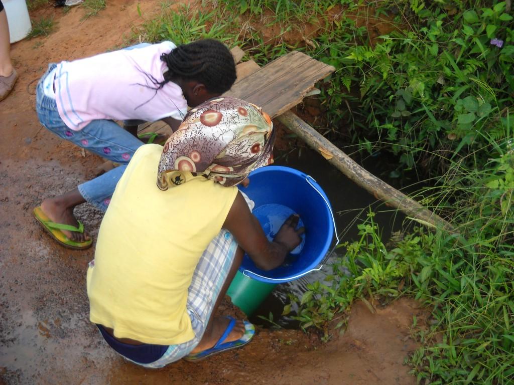 Rita och Angela gör rent hinkarna innan de fyller vatten i dem.